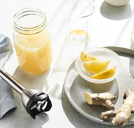 Lemon Ginger Juice with immersion blender sitting next to the glass